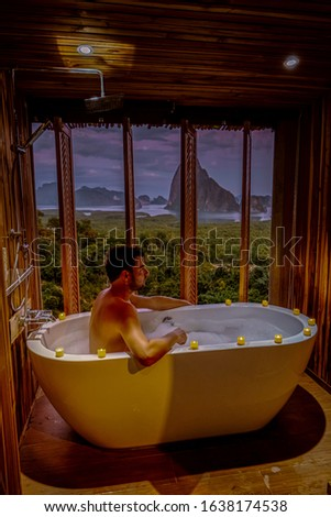 men in bathtub vacation Thailand watching sunsrise in the mountains looking over over ocean