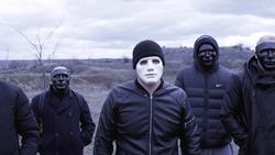 Men in black jackets and masks. Footage. Criminal gang in black plastic masks and leader in white mask on background of cloudy sky. Masked social criminal gang