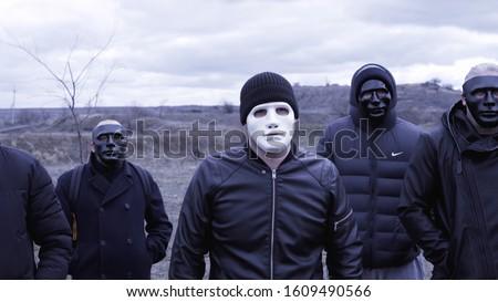 Photo of  Men in black jackets and masks. Footage. Criminal gang in black plastic masks and leader in white mask on background of cloudy sky. Masked social criminal gang