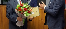 Men in business suits - officials, businessmen, teachers or lawyers - participants in the awards ceremony. Presentation of a certificate of honor and a bouquet of flowers. No face