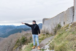 Men in Cathar castle of Montsegur in Ariege, Occitanie in south of France in winter 2020.