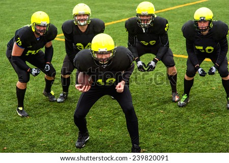 Men in green sportswear and helmet playing american football on the sports ground