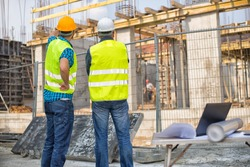 Men in hardhat and green jacket posing on building site