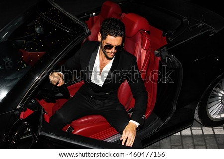 Men in luxury car. Night life.