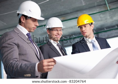 Men in suits at a construction site