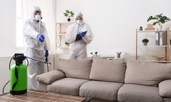 Men in virus protective suit making treatment of sofas and surfaces from coronavirus, preventive measures, copy space