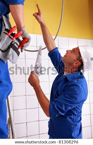 Men inspecting electrical installations - stock photo