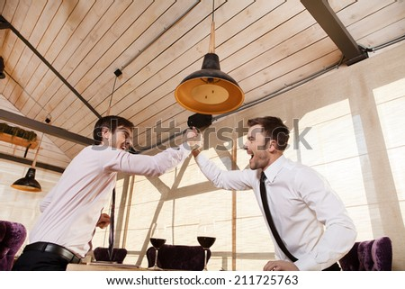 men laugh together while meeting in cafe. two man holding hands and greeting each other inside