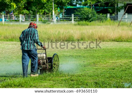 Men lawn mower with a long grass after the rain. #693650110