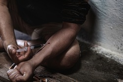 Men of a drug addict and a syringe with narcotic syringe sitting on the floor. Anti drug concept