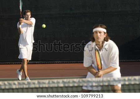 Men playing tennis at tennis court