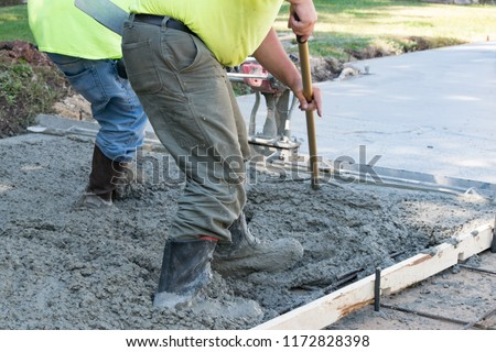 Men Pouring and Finishing a Concrete Slab Driveway with a Wet Cement Mix #1172828398