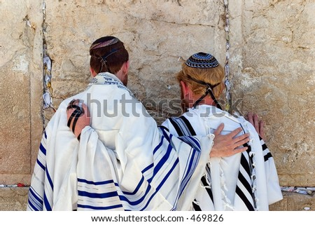 men praying at the wailing wall.