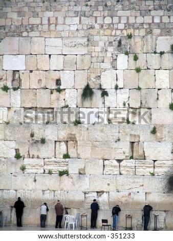 men praying at the western wall, the most holy site for the Jewish Culture.