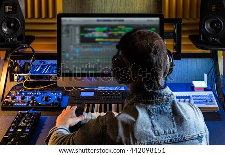 Men produce electronic music in project home studio.
