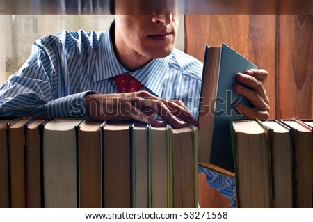 men put a book on to the bookshelf