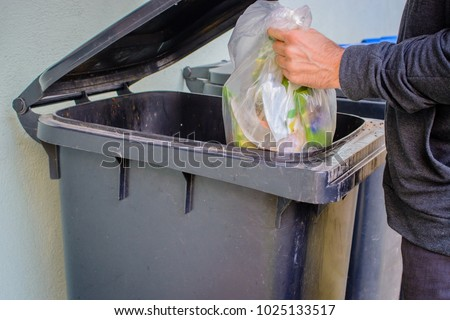 Men putting garbage in garbage bin (litter)