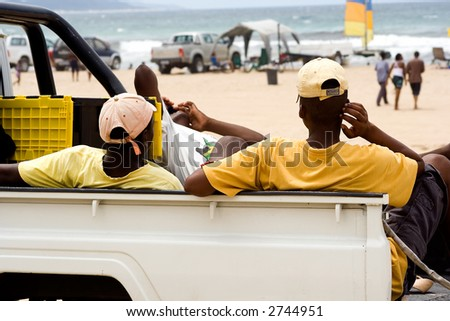 Men resting on back of truck at the beach.