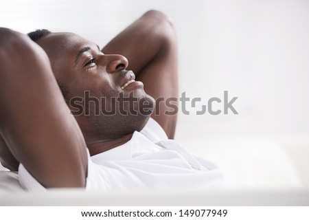 Men resting. Side view of happy African descent men sitting with his head in hands