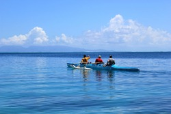 Men rowing a traditional outrigger canoe in French Polynesia