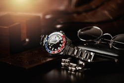 men's accessories, closeup at wristwatch with black dial blue-red bezel and stainless steel bracelet.