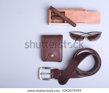 Men's accessories for business and recreation. Wallet, belt, glasses, cigar. Top view composition.