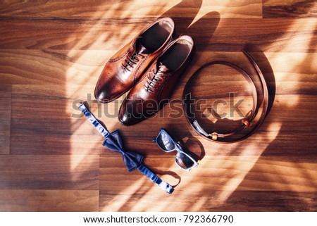Men's Accessories. Men's expensive shoes, fashion sunglasses, butterfly tie and leather belt on a wooden floor. Top view. #792366790