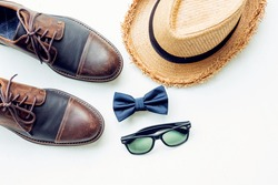 Men's accessories outfits with brown leather shoes, hat, sunglasses, and bow tie, top view, flat lay on wooden board background