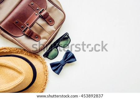 Men\'s accessories outfits with leather bag, sunglasses, hat, and bow tie, top view, flat lay on wooden board background