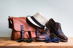 Men's accessories with brown leather bag, brown shoes, classic hat, sunglasses and blue bow tie on wooden table over wall background