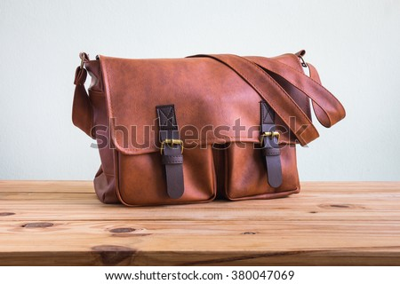 Men\'s accessories with brown leather bags on wooden table over wall background