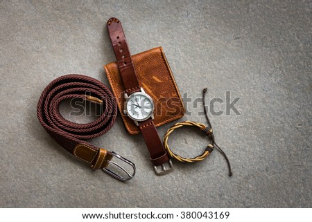 Men\'s accessories with brown leather wallet, belt and watch on gray background