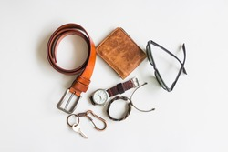 Men's accessories with brown leather wallet, belt, sunglasses, key and watch on white background