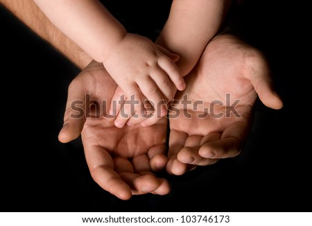 Men's and children's hand isolated on black background