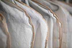 Men's and women's clothing hangs on hangers in white protective covers