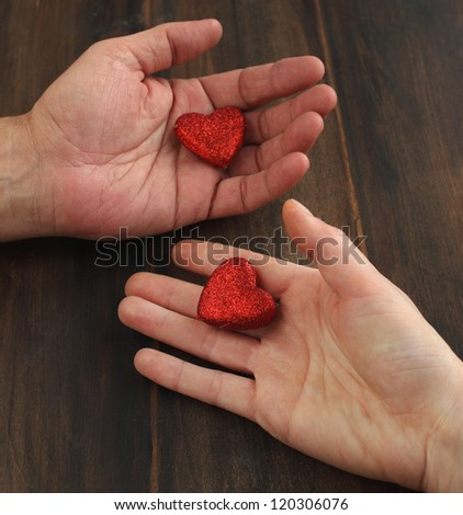 Men's and women's hands with a red heart
