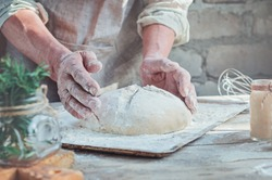 Men's baker's hands hold raw home-made bread, rustic style