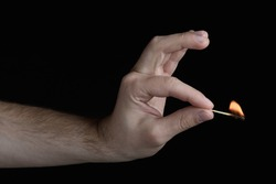 Men's black and white hand holding a burning match with a flame. isolated on black background closeup in pastel shades