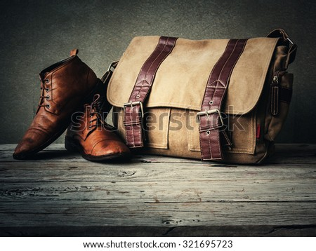 Men\'s boots and brown bag on wooden table over wall grunge background