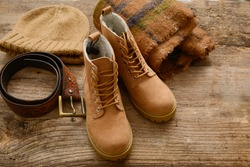 Men's brown leather boots. Stylish shoes ,and scarf, belt, straw hat isolated on old wooden background