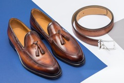 Men's brown leather shoes and belt on a colorful background