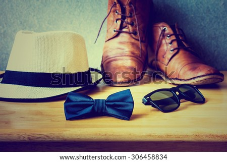 Men\'s casual, bow tie with sunglasses and boots on wooden over wall grunge background