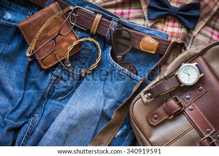 Men\'s casual outfits background, brown plaid shirt, bow tie, blue jeans, brown bag and stationary