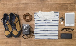 Men's casual outfits on wood board background, essential vacation item for traveler. On the wooden boards are shoes, belt, twin-lens reflex camera, e-book, T-shirt, keys, glasses and phone. Flat lay.