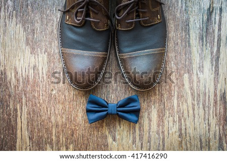Men\'s casual outfits with brown shoes and blue bowtie on rustic wooden background
