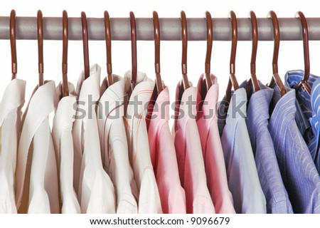Men's Dress Shirts on Hangers in closet isolated over white