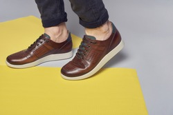 Men's fashion sport shoes. Shoes on legs. Advertisment concept. Footwear.  Comfortable, design , yellow and grey background