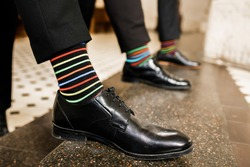 Men's feet in a row of shoes. Colored socks. Positive photo.