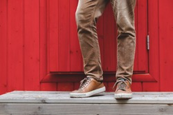 Men's feet in brown sneakers and brown corduroy trousers stand on the porch in front of the front door. The facade of the house is bright red.