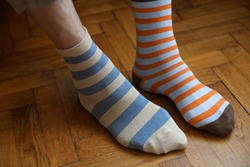 Men's feet in funny, colorful socks on a brown background